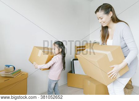 Happy Young Asian Mother And Her Daughter Child Girl With Cardboard Boxes In New House At Moving Day