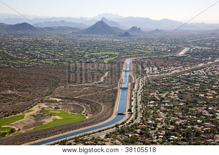 The Arizona Canal flowing past suburbs and golf courses in Scottsdale Arizona poster