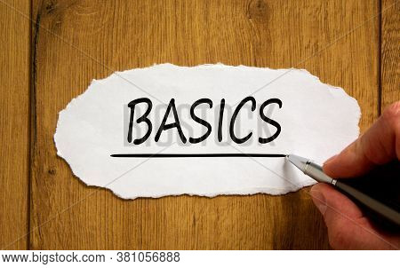 Male Hand Writing 'basics' On White Paper On Wooden Table. Business Concept.
