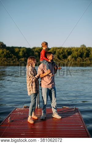 Happy Family Hugs Each Other Standing On Dock. Summer Photography For A Blog Or Advertising About Fa