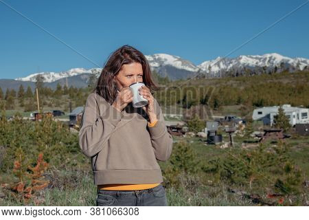Young Woman Holds Coffee Mug And Meets Cold Morning In Camping Place. Romantic Camp Traveling Concep