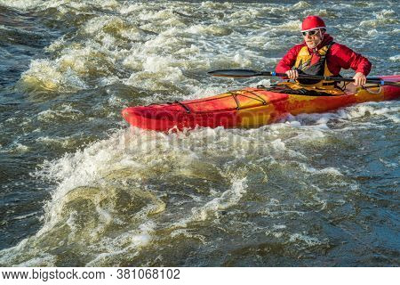 senior whitewater kayaker paddling upstream the river rapid - the Poudre River, Fort Collins, Colorado
