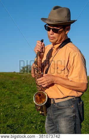An Alto Saxophone Player At A Park Adjusting The Mouthpiece.   Vancouver Bc Canada