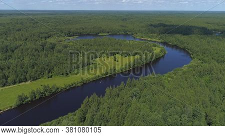 Aerial View Of The Bend Of The River Surrounded By Green Fields Through Which The River Flows. Shot.