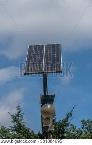 Small Solar Panel On Top Of Light Pole Above Treetops Against Blue Cloudy Sky.