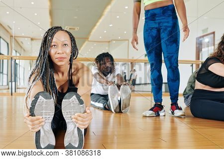 Smiling Black Young Woman With Dreadlocks Sitting On The Floor And Stretching Forward Touching Tipto