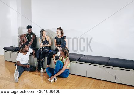 Multi-ethnic Group Of Young Dancers Discussing Performace And Gossiping After Training In Studio