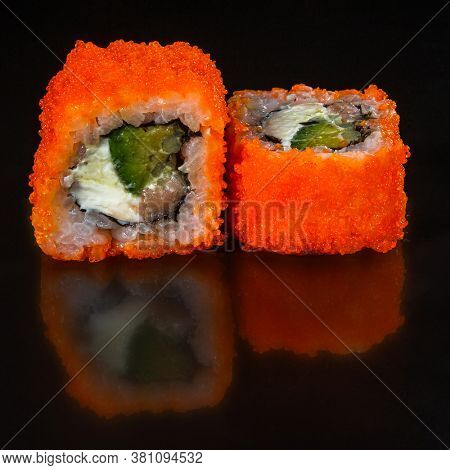 California roll sushi with salmon, cucumber, avocado, cream cheese, red masago caviar over black background. Sushi menu, Japanese food.