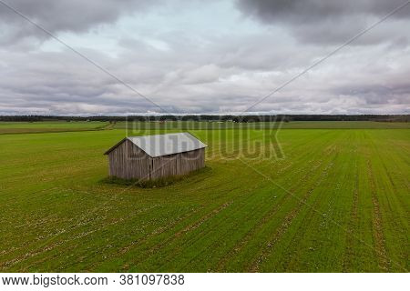 A Barn House Stands In The Middle Of A Huge Green Fields At The Rural Finland. The Sky Above Is Beau