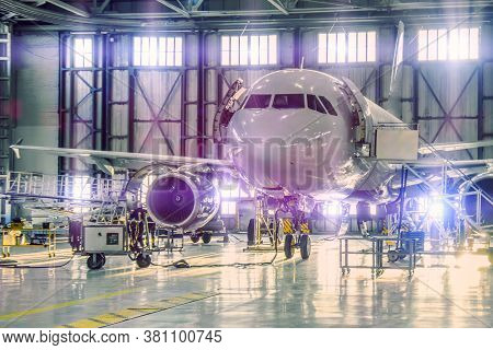 Civil Airplane Jet On Maintenance Of Engine And Fuselage Check Repair In Airport Hangar. Bright Ligh