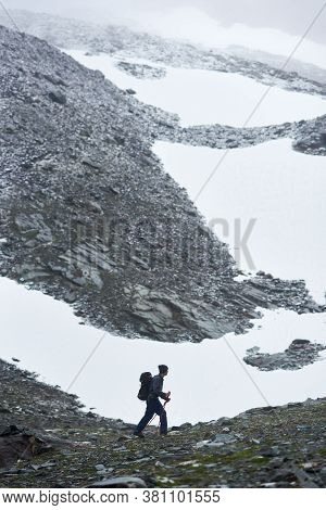 Male Hiker With Backpack And Trekking Poles Hiking In Snowy Mountains. Young Backpacker Walking Alon