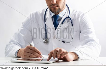 Close Up Of Male Doctor Hands Using Tablet Computer. Physician In White Medical Uniform With Stethos