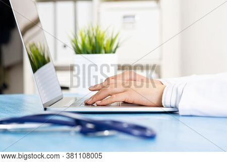 Close Up Of Female Doctor Hands Using Laptop Computer. Physician In White Medical Uniform Sitting At