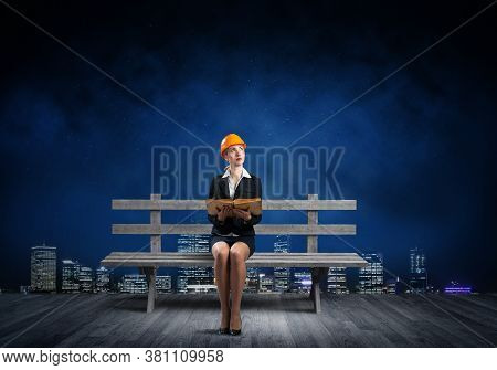 Beautiful Woman Architect Sitting On Wooden Bench Outdoors. Young Technician Specialist In Orange Sa