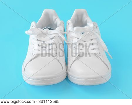 Pair Of New White Sneakers On Blue Background. New White Leather Sneakers Sports Shoes. Sports Shoes