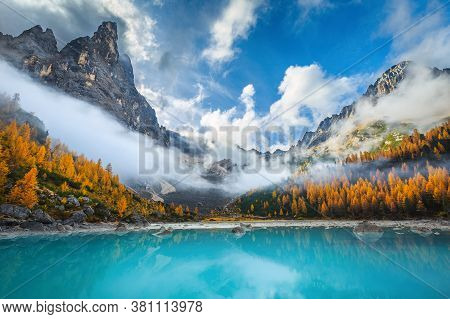 Beautiful Misty Mountains And Colorful Yellow Larches On The Shore Of The Lake Sorapis. Breathtaking
