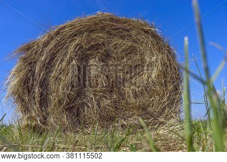 Haystack. Hay Bale On Green Lush Grass Against A Blue Sky. Harvesting Hay, Dry Grass