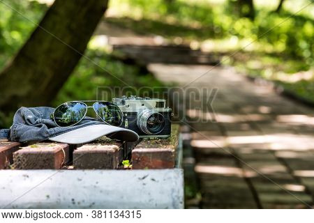 Vintage Phototographer Accesories On A Bench Un The Park. Rangefinder Old Camera, Sunglasses And A B