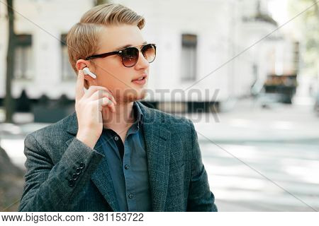 Cheerful Young Business Man Using Earpods In City And Looking Away