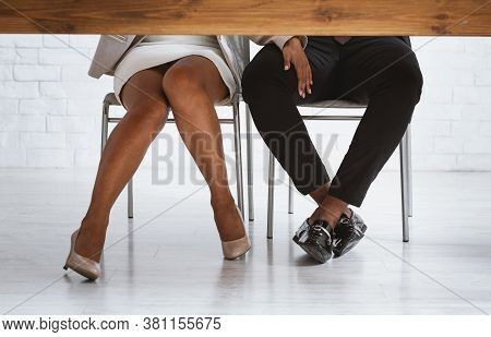 Closeup View Of Black Lady Boss Sexually Molesting Her Male Subordinate, Touching His Leg Under Tabl