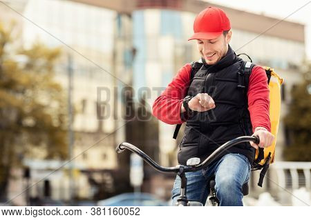 Happy Courier Checking Time On Wristwatch Delivering Food On-time Sitting On Bike In City. Delivery