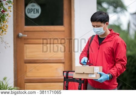 Close Up Delivery Man Wearing Blue Gloves In Red Cloth Searching For Customer Address By Mobile Phon
