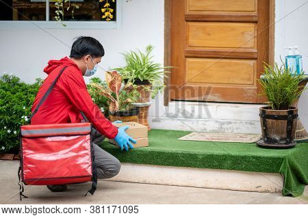 Delivery Man Wearing Blue Gloves In Red Cloth Holding A Box Package