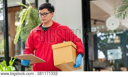 Delivery Man Wearing Blue Gloves In Red Cloth Holding Cardboard Boxes