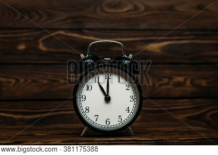 Clock On A Wooden Background. The Clock Shows The Time Of Eleven O'clock In The Afternoon. The Clock