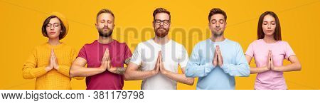 Peaceful Modern Young People In Casual Multicolored Clothes Standing With Namaste Gesture During Med