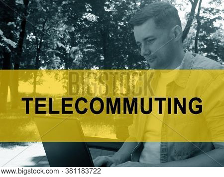 Telecommuting Concept. A Young Man Is Typing On A Laptop In The Park.