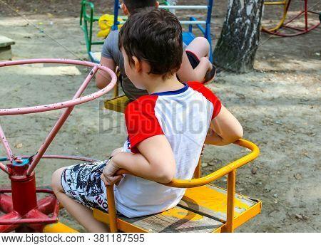 Children Spin On A Spinning Carousel On The Playground In Summer.