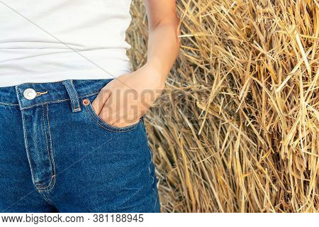 Close-up Young Adult Woman Hand In Blue Denim Jeans Pocket Shorts Or Pants Stand Against Hay Stack A