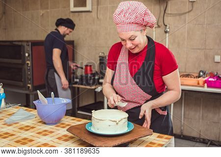 Female Chef In Red Work Wear In Pasty Shop Making White Fondant Cake. Her Male Assistant In Black Wo