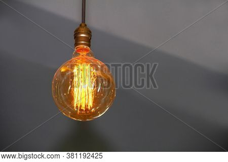 An Orange Circular Lamp On A Gray Background