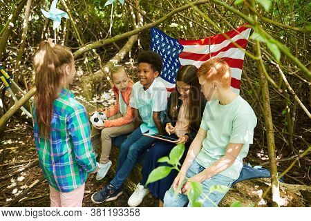 Multi-ethnic Group Of Kids Hiding Under Branches Of Big Tree While Playing In Forest Or Back Yard, C