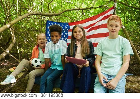 Multi-ethnic Group Of Kids Looking At Camera While Sitting Under Branches Of Big Tree And Playing In
