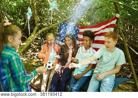 Multi-ethnic Group Of Kids Lighting Sparklers While Hiding Under Branches Of Big Tree In Forest Or P