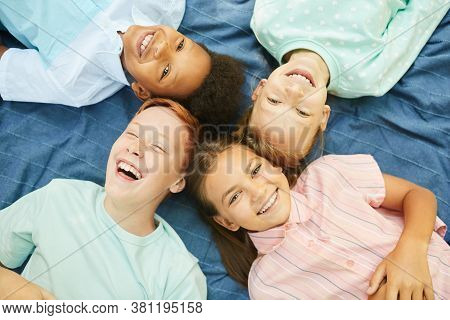 Top View Close Up Of Multi-ethnic Group Of Kids Lying In Circle On Blanket Outdoors And Looking At C