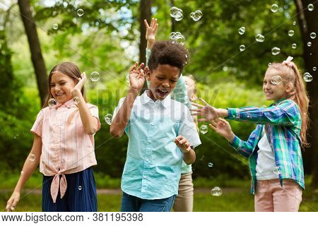 Waist Up Portrait Of Multi-ethnic Group Of Carefree Children Playing With Bubbles Outdoors In Park