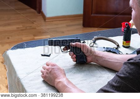 A Man At Home Holds A Gun In His Hands. A Man With A Pistol.
