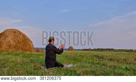 A Muslim Senior Man Wearing A Skullcap And Traditional Clothes Prays In An Hayfield.