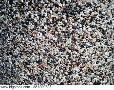 Small Stones Of Different Colors As Decoration On The Wall. Fine Sand Beach And Stone. Warm Natural
