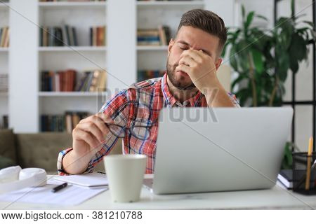 Unhappy Frustrated Young Male Holding Head By Hands Sitting With Laptop Behind Desk At Home.