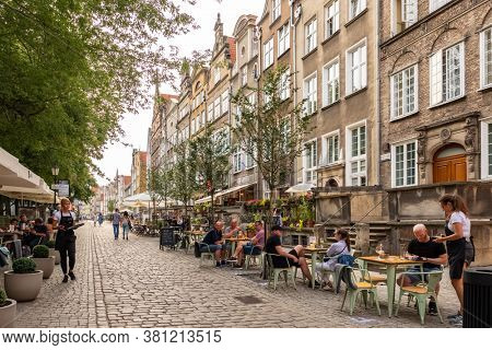 Gdansk, Poland - July 22, 2019: Cozy outdoor cafe in Gdansk old town, Poland. Unidentified people seats in outdoor cafe in central part of Gdansk