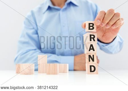 Business brand building or branding for company identity and marketing businessman stacking wood cube blocks with letters