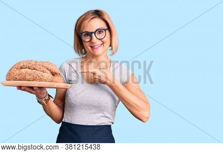 Young blonde woman holding wholemeal bread smiling happy pointing with hand and finger