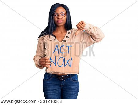 Young african american woman holding act now banner with angry face, negative sign showing dislike with thumbs down, rejection concept