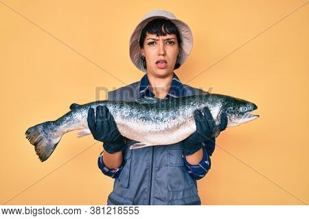 Beautiful brunettte fisher woman showing raw salmon clueless and confused expression. doubt concept.