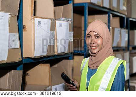 Portrait of Islam Muslim female warehouse worker hold barcode scanner in front of product shelf with stock card in warehouse distribution. For business warehouse inventory and logistic concept.